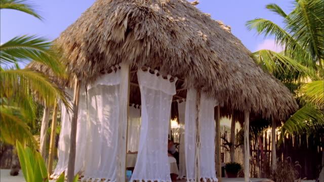 vídeos de stock e filmes b-roll de curtains sway in breeze as woman performs massage in thatched beach hut, belize available in hd. - telhado de palha