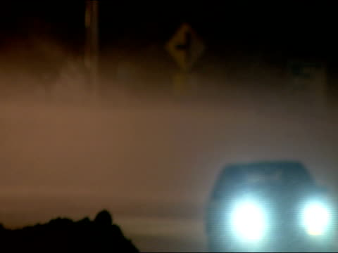 vidéos et rushes de curve on small town road, snow blowing over roadway like dust, cars passing. sparse traffic, dangerous driving conditions. - phare de véhicule