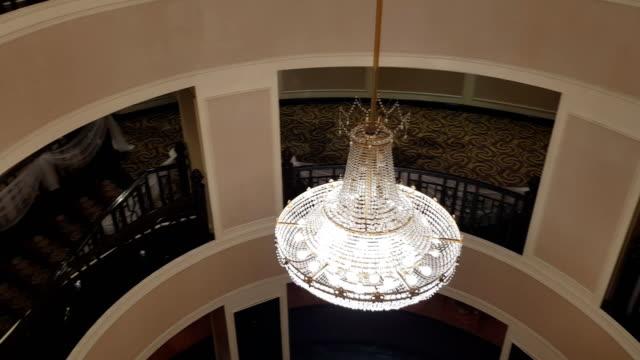 vidéos et rushes de courbe panoramique chrystal lustre en gros plan. fond de glamour avec copie espace et salle - lampe électrique
