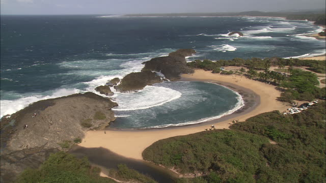 A curved beach surrounds a natural cove in Puerto Rico.