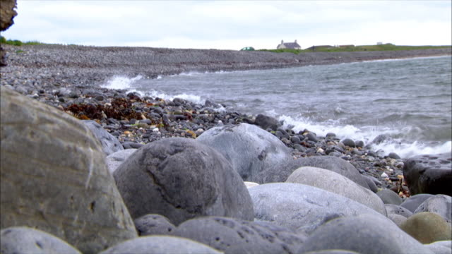 curved irish sea seashore shoreline w/ small rocks shoreline, small boulders fg, rocky beach & distant house & roofs bg. - isle of man stock videos & royalty-free footage
