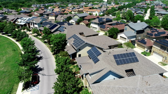 vídeos de stock e filmes b-roll de curved layout mueller new development suburb with rooftop solar panels in austin , texas - close to far backing away from solar rooftops on houses - painel solar