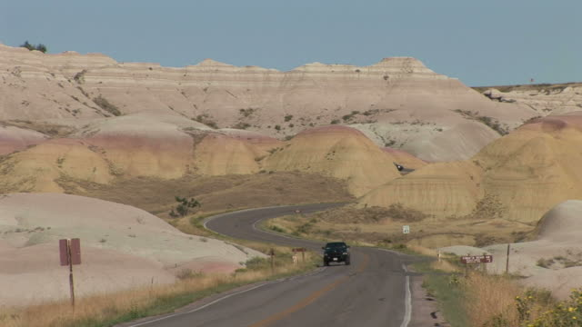 curved road in badlands national park united states - badlands national park stock videos & royalty-free footage