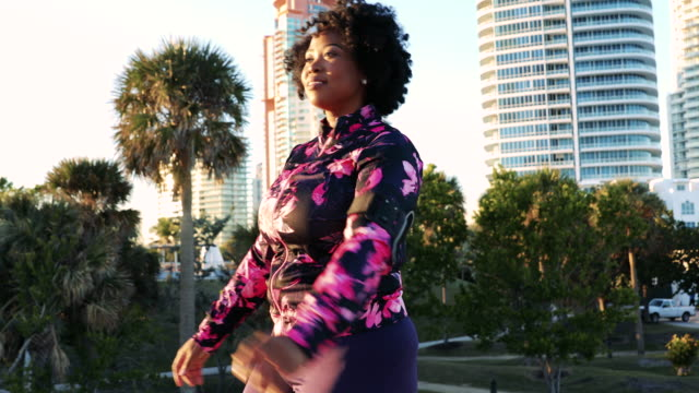 Curvy young black woman relaxation exercise and stretching in Miami Beach public park