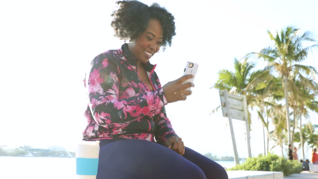 curvy young black woman taking a break from the workout session chatting on mobile - mid adult stock videos & royalty-free footage