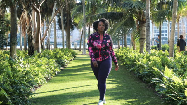 Curvy young black woman walking, jogging and running in Miami Beach public park