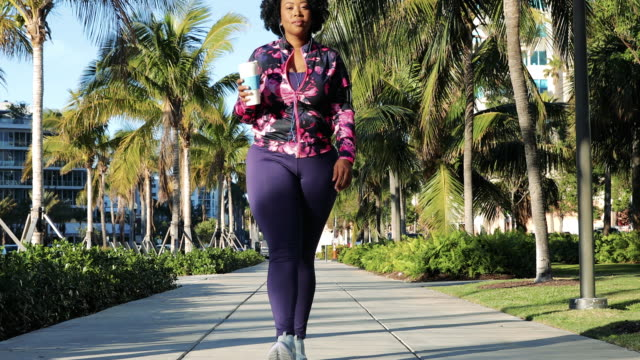 curvy young black woman walking, jogging and running in miami beach public park - overweight stock videos & royalty-free footage