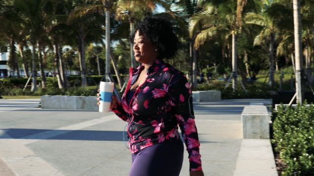 curvy young black woman walking, jogging and running in miami beach public park - plus size model stock videos & royalty-free footage