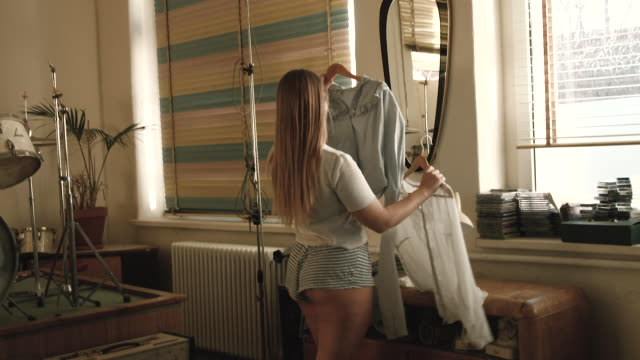 curvy young woman deciding what to wear - coathanger stock videos & royalty-free footage