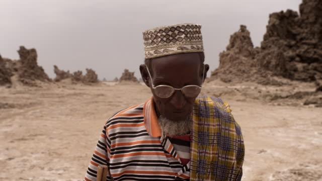 cus elderly afar man walks over barren landscape - horn of africa stock videos & royalty-free footage