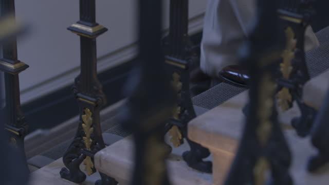 cus man walking down grand, carpeted stairs - railings stock videos & royalty-free footage