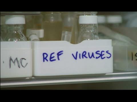 vídeos de stock, filmes e b-roll de / cus of lab technician taking virus samples out from refrigerator ecu of labels indicating origin of samples / technician putting on rubber gloves... - gripe suína