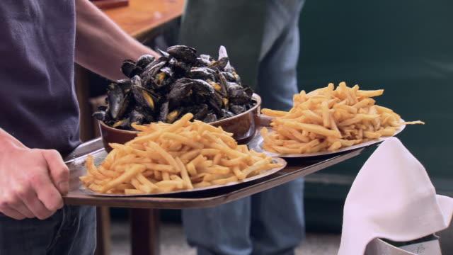 cus people eating moules-frites, france - ムール貝点の映像素材/bロール