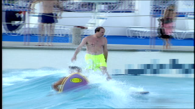 cus people trying to ride waves in wave pool with surf boards in palm springs california - palm springs california pool stock videos & royalty-free footage