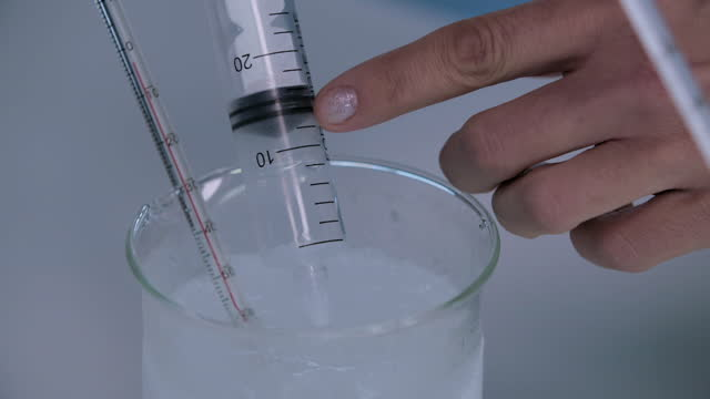 cus scientist conducts temperature experiment - volume fluid capacity stock videos & royalty-free footage