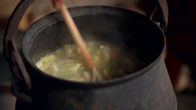 cus stirring soup in an old-fashioned cauldron - crucifers stock videos & royalty-free footage