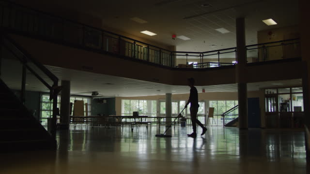 custodian sweeping floor in empty school hall - back lit stock videos & royalty-free footage