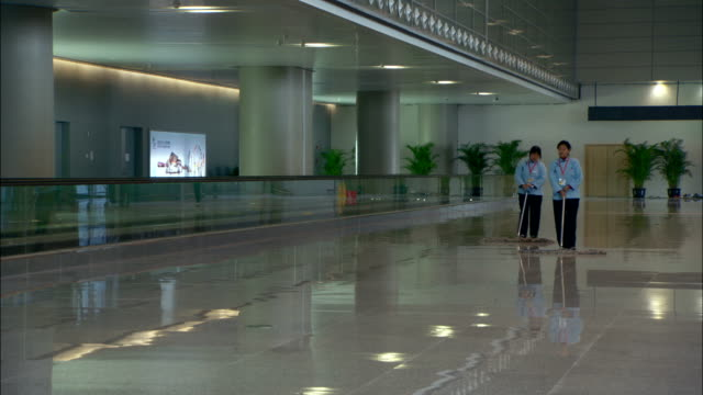 custodians sweep a glossy floor in the shanghai hongqiao transit hub. - caretaker stock videos & royalty-free footage