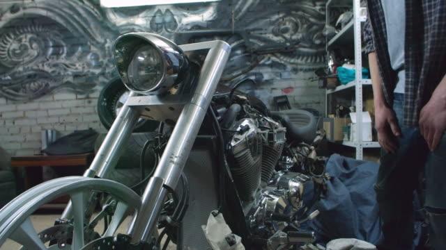 custom motorcycle builder examining a bike - bedecken stock-videos und b-roll-filmmaterial