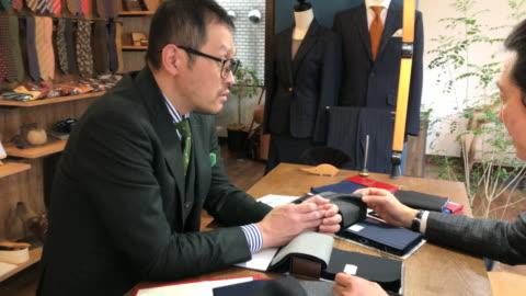 stockvideo's en b-roll-footage met aangepaste pak shop in tokyo - klanten georiënteerd