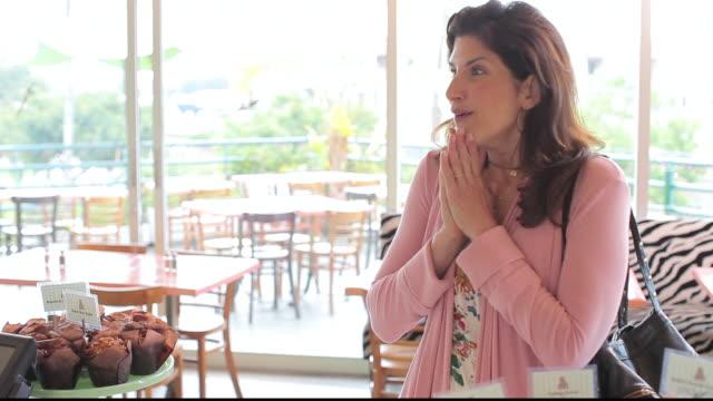 vídeos de stock e filmes b-roll de ms customer admiring giant cupcake in bakery / los angeles, california, united states - admiração