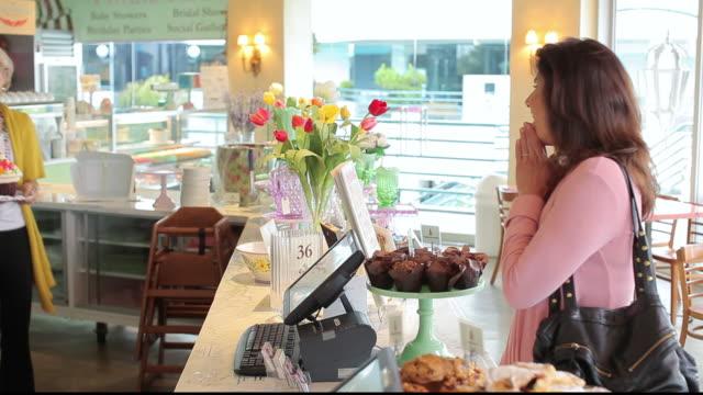 stockvideo's en b-roll-footage met ms customer admiring giant cupcake in bakery / los angeles, california, united states - breedbeeldformaat