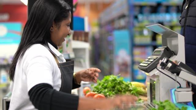 顧客とスーパー マーケットでのチェック アウトでレジ係