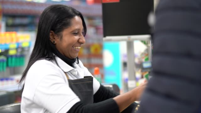 customer and cashier in checkout at supermarket - shop assistant stock videos & royalty-free footage
