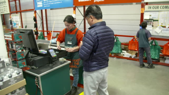 Customer and employees with bar code reader and EFTPOS terminal at checkout area at Bunnings Warehouse hardware store