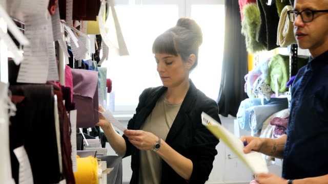 customer and manager examining fabrics in rack - rolled up stock videos & royalty-free footage