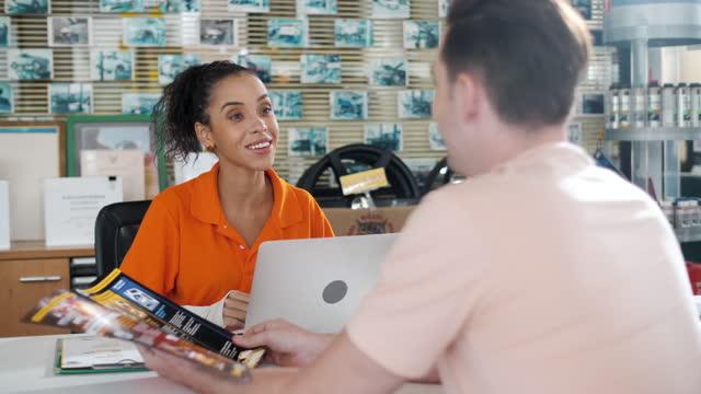 vidéos et rushes de client et vendeuse présentant brochure au service de voiture - partie de véhicule