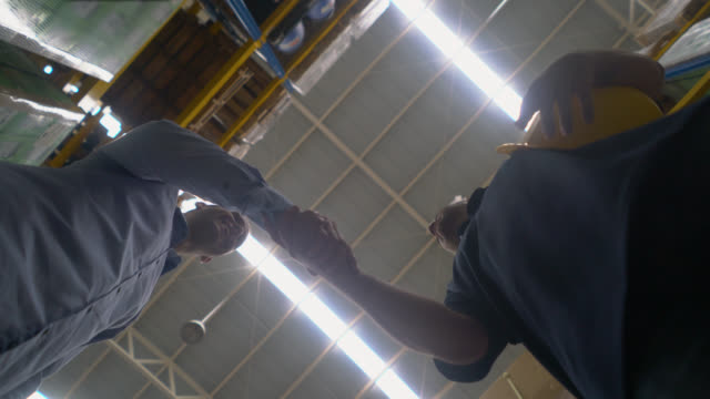 Customer and worker at a warehouse talking and customer thanking him with a handshake