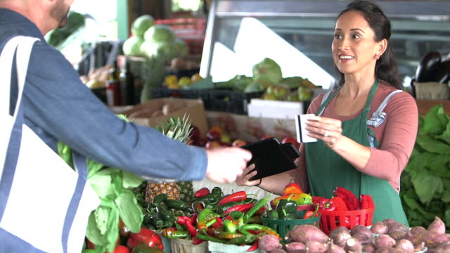 customer at produce stand paying with credit card - paying stock videos & royalty-free footage