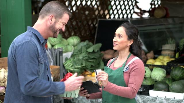 vídeos de stock e filmes b-roll de customer at produce stand paying with credit card - mercado de produtos agrícolas