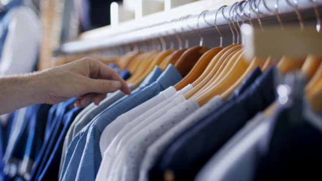 Customer browses rack and picks out shirt at modern clothing store