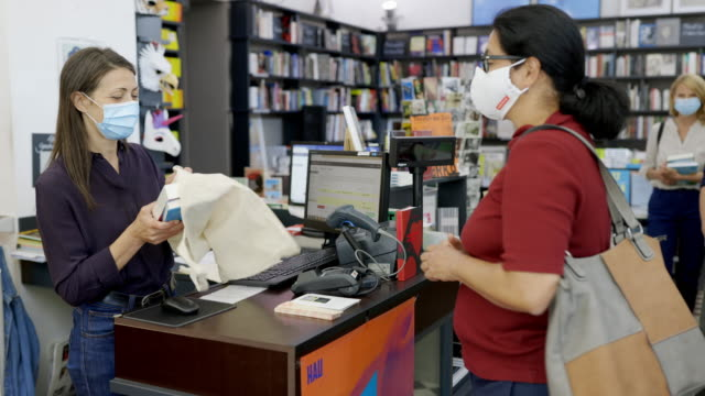 customer buying books at bookstore during pandemic - book shop stock videos & royalty-free footage
