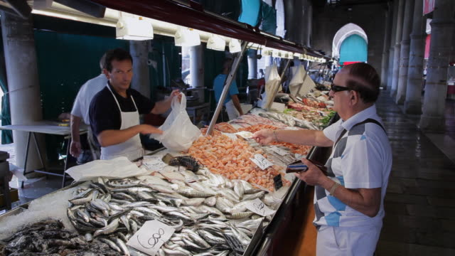 mh customer buying fish in market / venice, italy - fish market stock videos and b-roll footage