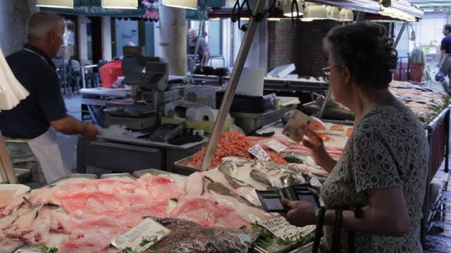 mh customer buying fish in market / venice, italy - pesce video stock e b–roll