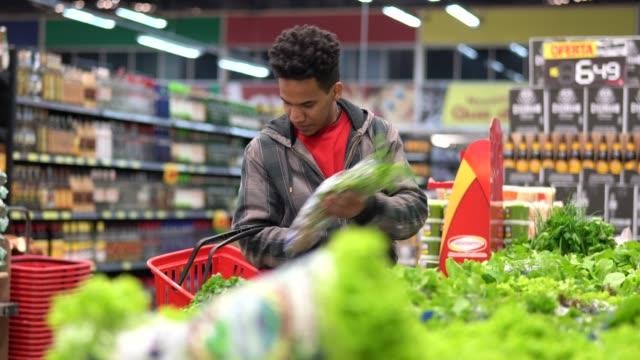 customer buying greens on supermarket - vegetarian food stock videos & royalty-free footage