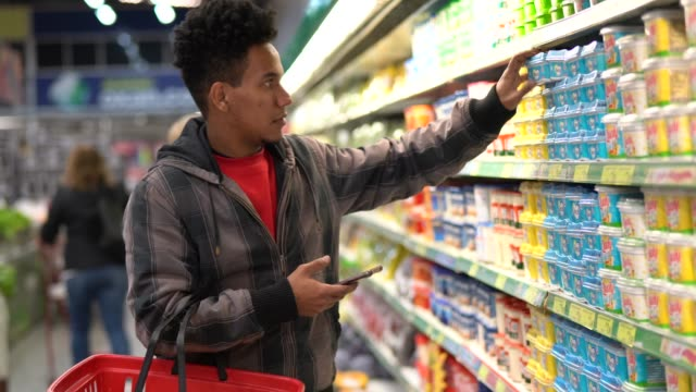 vídeos de stock e filmes b-roll de customer buying with mobile app on supermarket - comércio consumismo