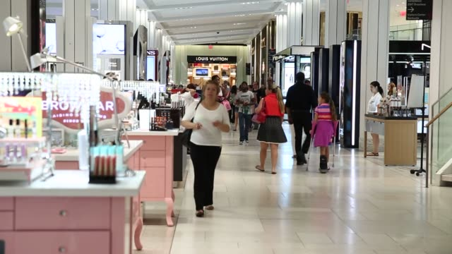 A customer carries a shopping bag while walking through the Macys Inc flagship store in New York US Customers shop in the cosmetics section at the...