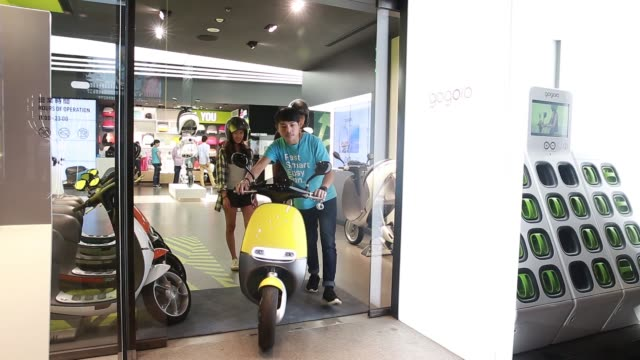 vidéos et rushes de customer changes batteries on a gogoro inc, smartscooter outside the company's global experience center in taipei, taiwan, on tuesday, june 28 an... - essai de voiture