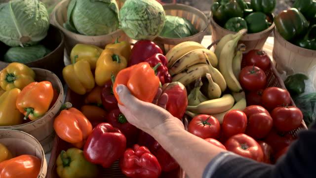 customer checks damaged vegetables and picks an orange bell pepper - marcio video stock e b–roll