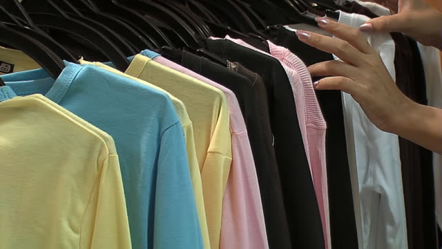 customer chooses t-shirt in clothes shop - nightwear stock videos & royalty-free footage
