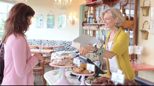 stockvideo's en b-roll-footage met ms customer choosing baked goods to buy in bakery cafe / los angeles, california, united states - breedbeeldformaat
