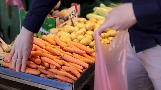 vidéos et rushes de le client choisit des carottes et les met dans le sac en plastique au marché fermier - étal de marché