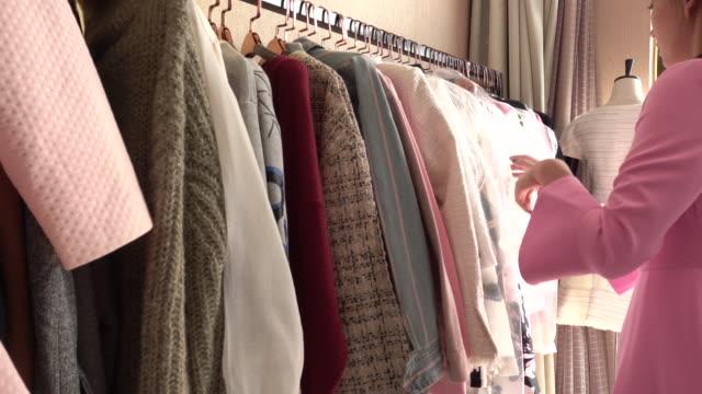 stockvideo's en b-roll-footage met customer choosing clothes at store - kledingrek
