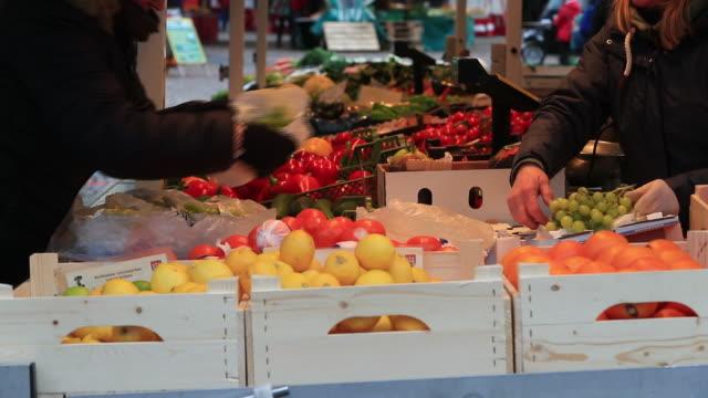 customer choosing fruit at street market, lüneburg, germany, on wednesday, february 12, 2020. - リューネブルグ点の映像素材/bロール