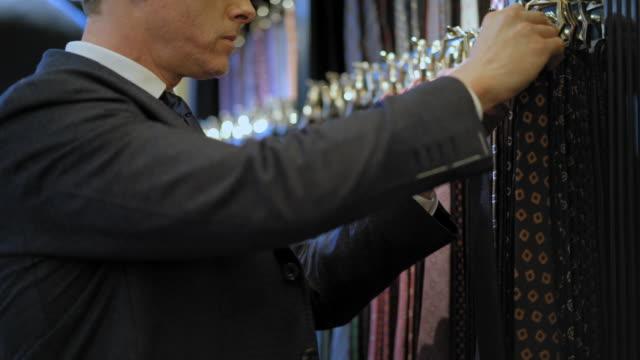vidéos et rushes de customer choosing necktie - costume complet