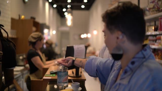 vídeos de stock, filmes e b-roll de cliente limpando as mãos com álcool gel - pushing